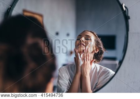 Woman In The Bathroom Washing Her Face With Foam