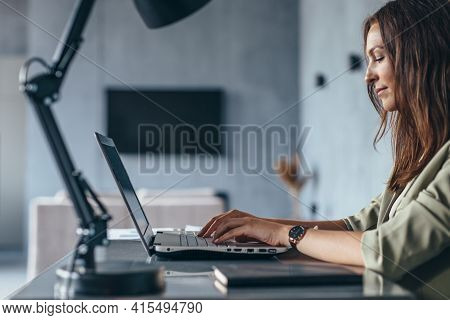 Woman Works At Home Sitting At Her Desk With Her Laptop. Side View
