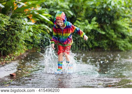 Kid Playing In The Rain In Autumn Park. Child Jumping In Muddy Puddle On Rainy Fall Day. Little Boy