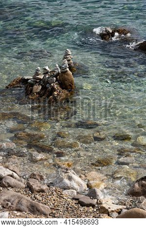 Stone Pyramids Stacked On The Seashore. Stack Of White Stones On Tropical Beach