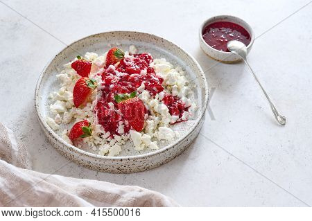 Cottage Cheese With Jam And Strawberries In Plate On Light Background. Nearby Raspberry Confiture Wi