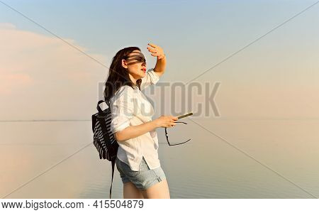 Side View Of Carefree Female Standing Near Sea And Covering Face From Sun At Sundown