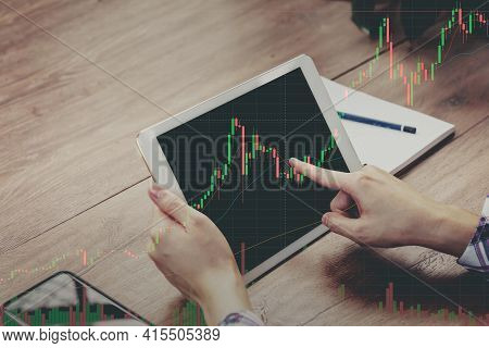 Trader Holding In Hands Tablet Researching Stock Market To Proceed Right Investment Solutions.