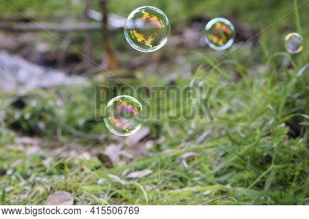 Soap Bubbles On An Abstract Background. Blurred Image. Multicolored Soap Bubbles On A Background Of