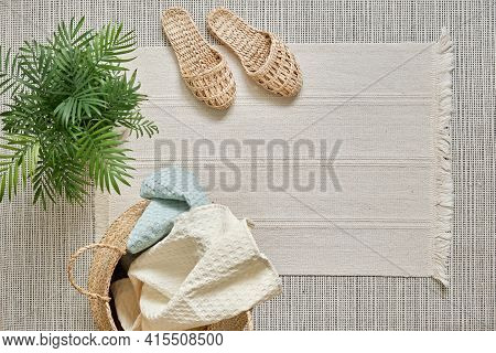 Natural Muslin Home Towels, White And Soft Blue, Lie In A Wicker Basket Against A White Cotton Rug A