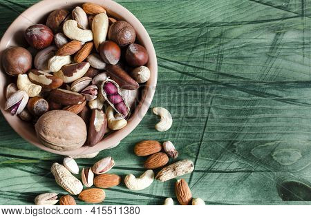 Assorted Nuts In Ceramic Dishes And Nuts Scattered On A Wooden Background Top View Assorted Nuts