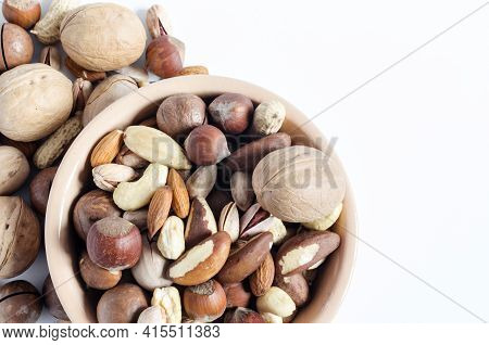 Assorted Nuts In Ceramic Dishes And Nuts Scattered On A White Background Top View Assorted Nuts