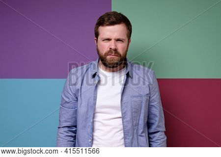 Man Frowned And Narrowed His Eyes And Sternly Looking At The Camera. Colorful Background.