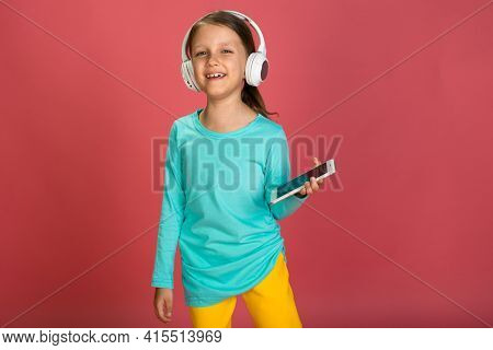 Little Beautiful Baby Girl Pink Background Bright Clothes Yellow Pants Turquoise Blue Shirt Wearing White Headphones Listening To Music And Dance With Smartphone In Hand