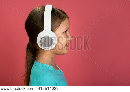Little Beautiful Baby Girl Pink Background Bright Clothes Yellow Pants Turquoise Blue Shirt Wearing White Headphones Listening To Music Profile Portrait