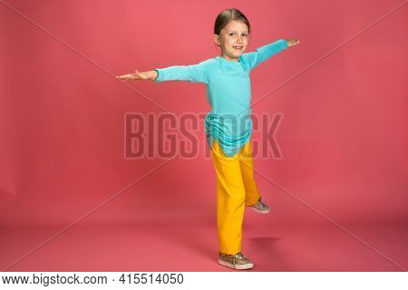 Little Beautiful Baby Girl Pink Background Bright Clothes Yellow Pants Turquoise Blue Shirt Spread her arms to the sides