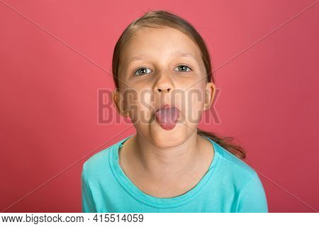 Little Beautiful Baby Girl Pink Background Bright Clothes Yellow Pants Turquoise Blue Shirt Make Faces