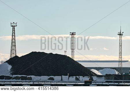 Coal Heap, Natural Black Coal, Product Of Mining And Three Towers With Searchlights. Industrial Land