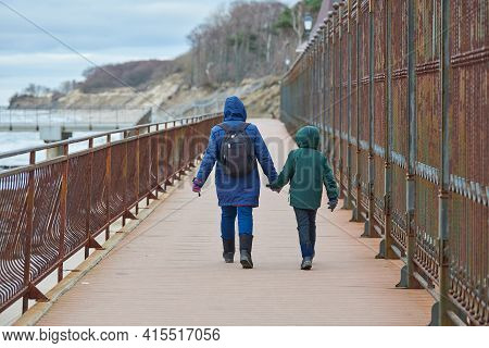 Back View Of Mother And Son Walking Along Quay Near Winter Sea. Seaside Trip, Woman And Boy In Down