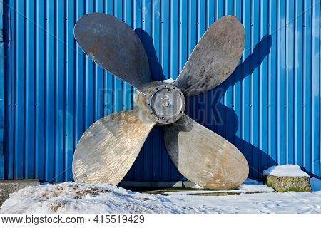 Old Boat Propeller Deteriorate In Boat Yard In Winter. Rusty Ship Propeller On Blue Wall Background.