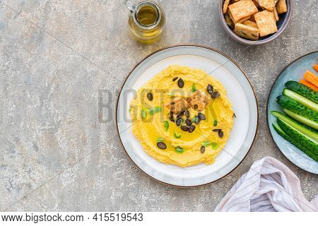 Healthy Snack, Chickpea Hummus With Pumpkin Or Carrots And Pumpkin Seeds On A Ceramic Plate On A Gra