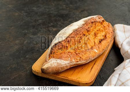 A Whole Loaf Of Homemade Wheat Bread On A Wooden Board Against A Dark Concrete Background.