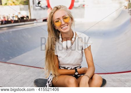 Laughing Skater Girl In Yellow Sunglasses Posing Outdoor. Photo Of Ecstatic Fair-haired Lady Sitting