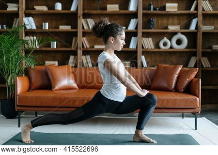 Profile View Of Barefoot Young Afro American Woman In Sportswear Stretching Legs, Doing Lunge Traini