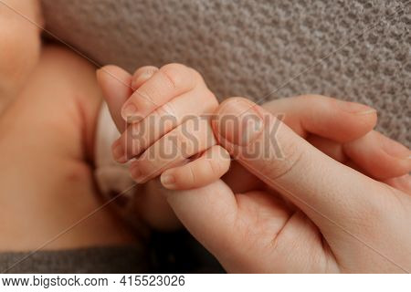 The Newborn Is Holding A Finger Of Mother On A Gray Background. Close-up. The Newborn Squeezes A Fin