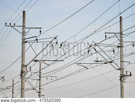 Catenary Railway Traction. Overhead Line, Electricity Pylons On Railway Track Against Blue Sky. High