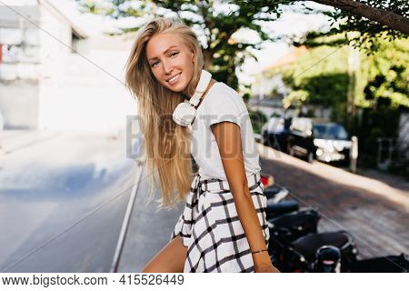 Relaxed Young Woman With Suntan Posing With Amazing Smile While Standing Near Road. Outdoor Photo Of