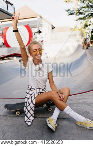 Graceful Tanned Skater Girl Waving Hand During Photoshoot. Cheerful Blonde Woman In White T-shirt Si