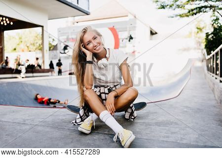 Gorgeous Woman In Cute White Socks Posing With Longboard. Outdoor Shot Of Smiling Blonde Skater Girl