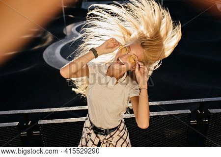 Lovable Girl In Trendy Casual Attire Funny Dancing On Urban Background. Happy Fair-haired Lady Fooli