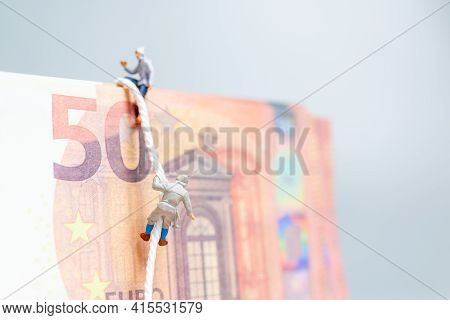 Miniature People , Climber Climbs On A Euro  Banknote Business Concept.