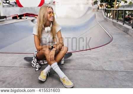 Amazing Girl In Big Headphones Sitting On Skateboard. Outdoor Portrait Of Lovely Blonde Female Model