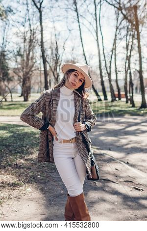Beautiful Woman Wearing Stylish Blazer, Hat And Boots Holding Purse In Park. Spring Female Fashionab