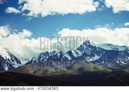 Awesome Mountains Landscape With Sunlit High Snowy Pinnacle Among Low Clouds In Blue Sky. Atmospheri