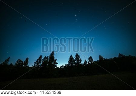 Dark Atmospheric Forest Landscape With Fir Tops Under Night Starry Sky. Wild Forest Silhouette On Mo