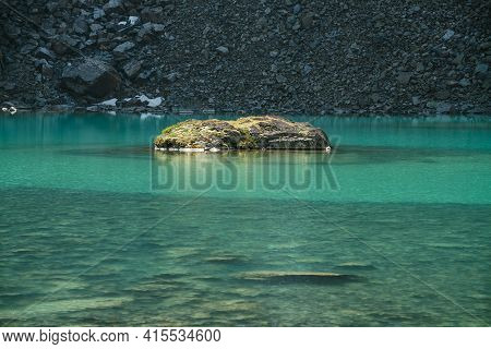 Beautiful Landscape With Mossy Rock In Turquoise Mountain Lake With Transparent Water And Stony Bott