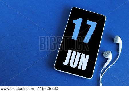 June 17. 17 St Day Of The Month, Calendar Date. Smartphone And White Headphones On A Blue Background