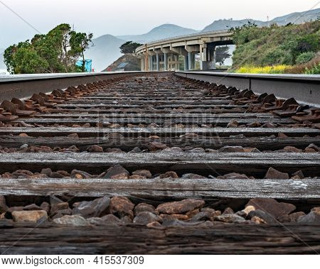Railroad Ties And Rocks Fill The Train Tracks Leading Up To The Roadway Bridge Along The Journey.