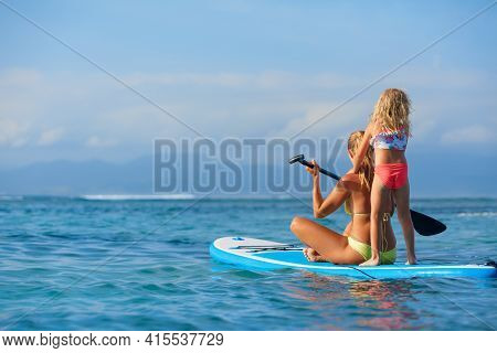 Active Paddle Boarder At Sunset Sea. Young Mother With Little Clild Paddling On Stand Up Paddleboard