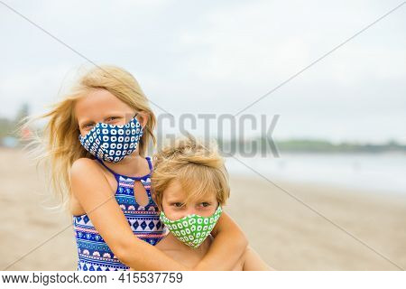 Children In Stylish Masks Have Fun On Sea Sand Beach. New Rules To Wear Face Covering At Public Plac