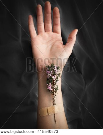 Close-up Of Woman's Open Hand With Flowers Attached To Her Forearm With Adhesive Bandage On A Wrinkl