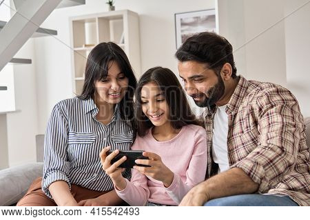 Happy Indian Family And Teen Child Daughter Using Smart Phone At Home. Smiling Teenage Kid Girl Show