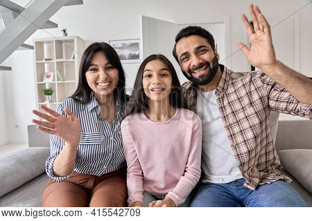 Happy Indian Couple And Teen Child Daughter Waving Hands Looking At Camera Sitting On Couch At Home.