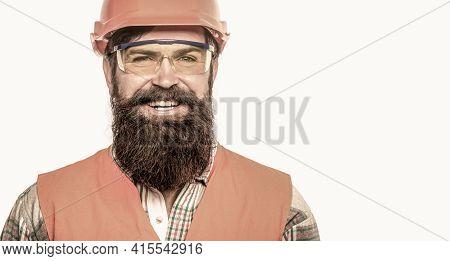 Portrait Of A Builder Smiling. Bearded Man Worker With Beard In Building Helmet Or Hard Hat. Buildin