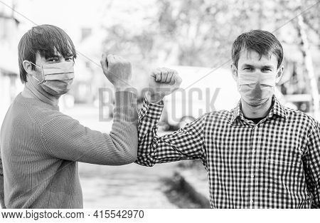 Friends Medical Mask. Elbow Bump. Elbows Bump. Friends In Protective Medical Mask On His Face Greet
