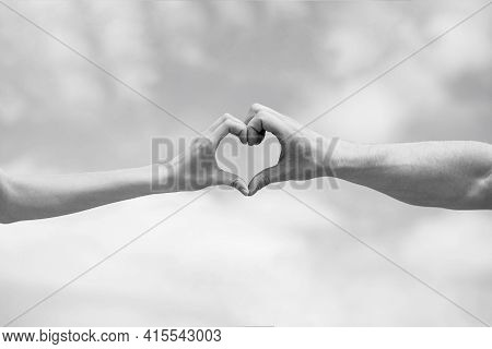 Female And Man Hands In The Form Of Heart Against The Sky. Hands In Shape Of Love Heart. Heart From