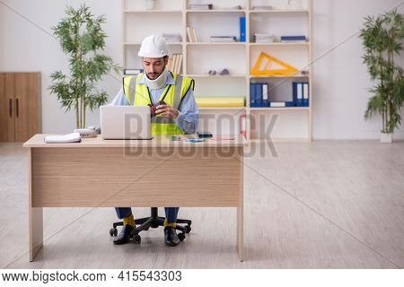 Young neck injured male architect in safety concept