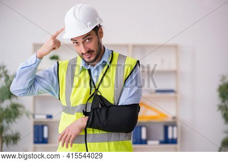 Young arm injured male architect working in the office