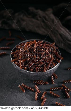 Organic Uncooked Buckwheat Fusilli Pasta On Dark Background. Wholegrain Gluten Free Noodles. Healthy