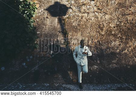 A Dapper Bald Bearded Black Guy In A Fashionable White Costume And Eyeglasses Is Waiting For His Gir
