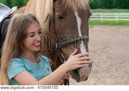 Young Caucasian Woman On Horse Back. Horseback Riding As Hobby In Paddock On Woods. Green Trees Fore